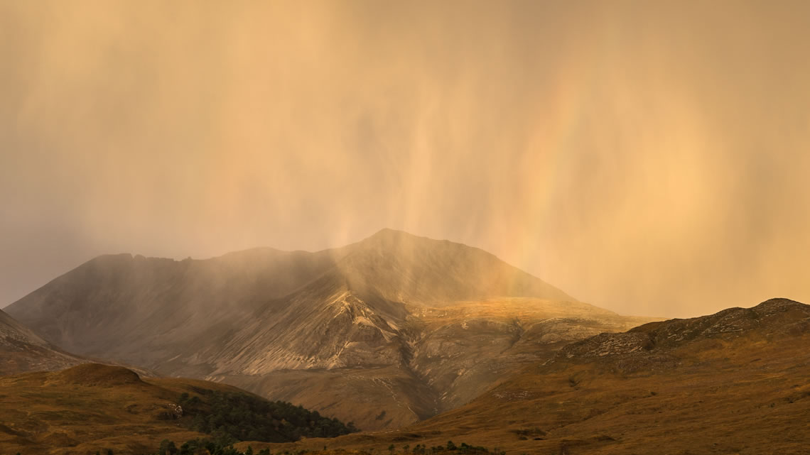 The morning sun shines through a rain shower in Glen Torridon